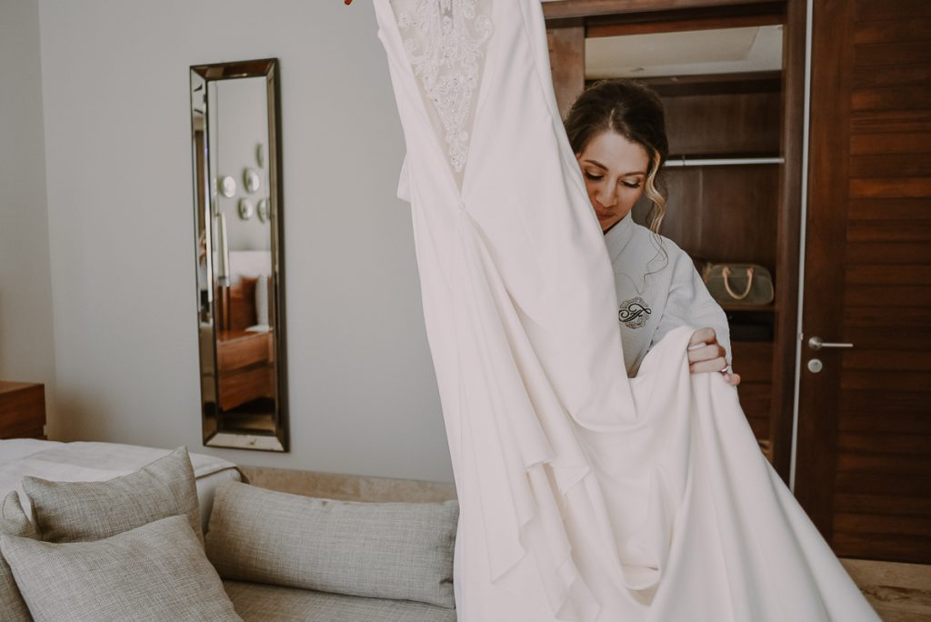 Bride getting into her wedding dress at Heritage Fairmont Mayakoba. Caro Navarro Photography