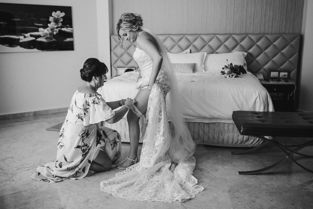 Mother of the bride placer the garter on bride. Moon Palace Wedding by Caro Navarro Photography