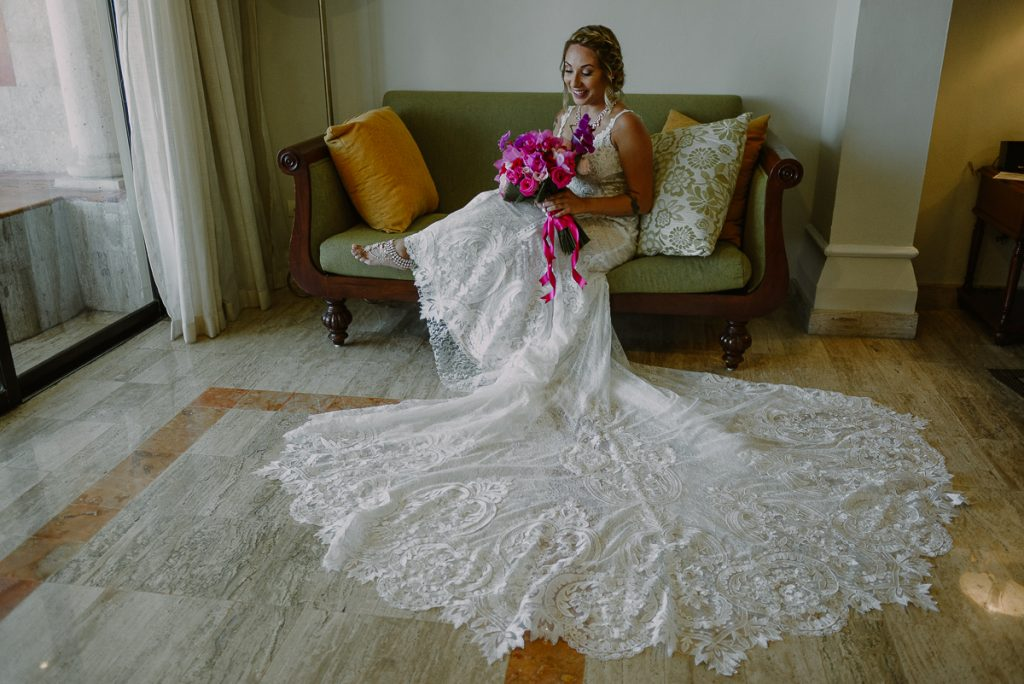 Bride with long tail wedding dress and hot pink bouquet at Now Sapphire Riviera Cancun. Caro Navarro Wedding Photography