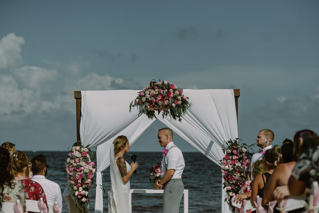 Bride and groom under white chuppah. Now Sapphire Riviera Cancun Wedding in Mexico. Caro Navarro Photography