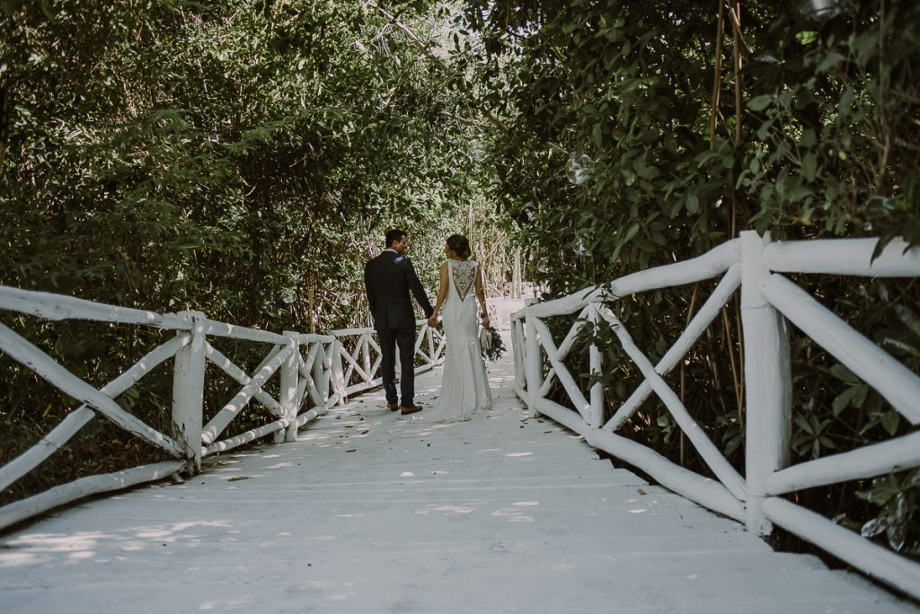 Bride and groom portraits on white bridge at Banyan Tree Mayakoba, Mexico. Caro Navarro Photography