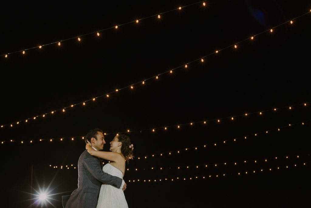 Bride and groom first dance with string lights at Jardin del Carmen Wedding in Mexico. Caro Navarro Photography