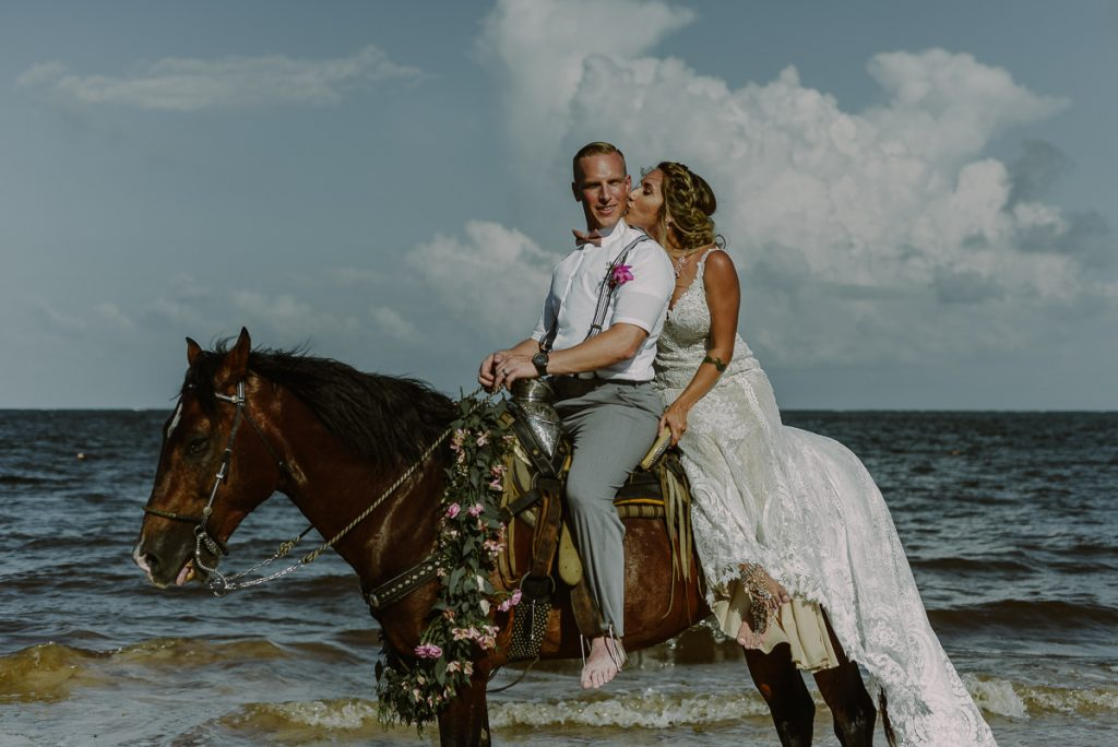 Bride and groom beach portraits on horse at Now Sapphire Riviera Cancun. Caro Navarro Photography