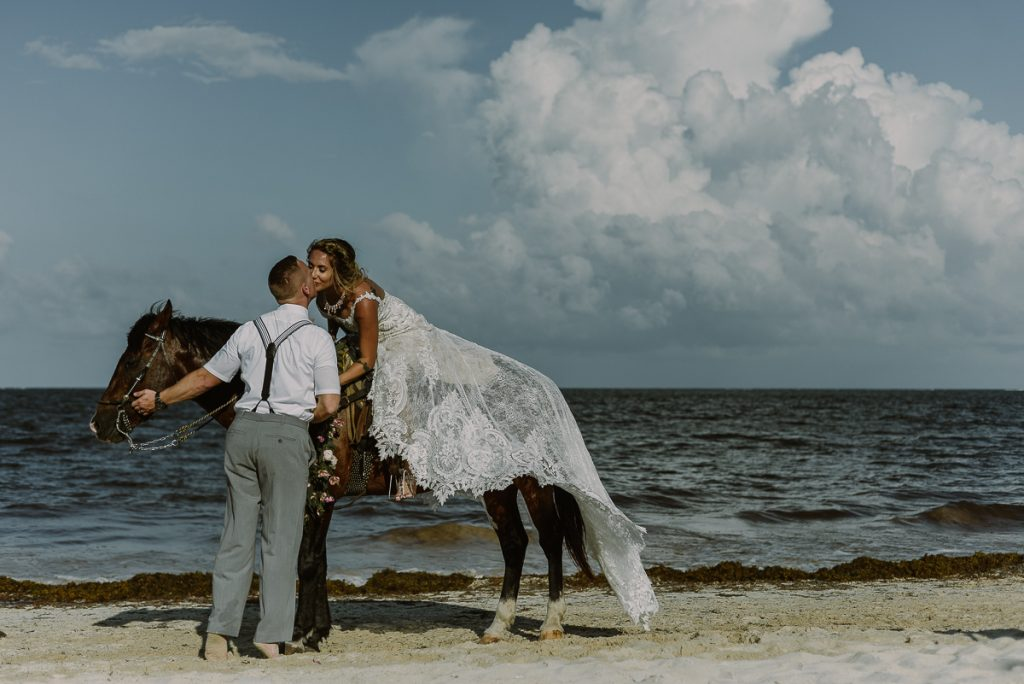Bride and groom beach portraits on a horse at Now Sapphire Riviera Cancun, Mexico. Caro Navarro Photography