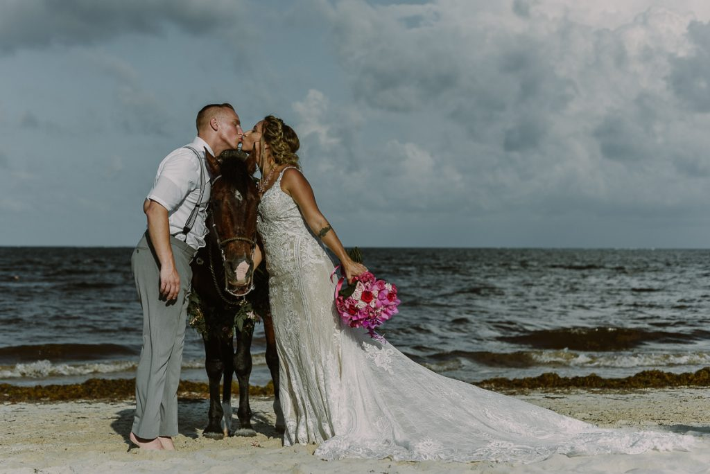 Beach bride and groom kiss with horse at Now Sapphire Riviera Cancun. Caro Navarro Wedding Photography