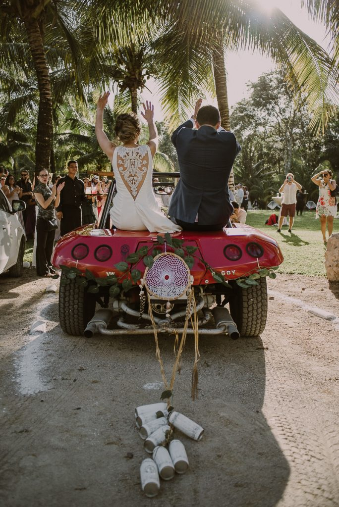 Bride and groom reception entrance in red buggy. Caro Navarro Mexico Wedding Photography