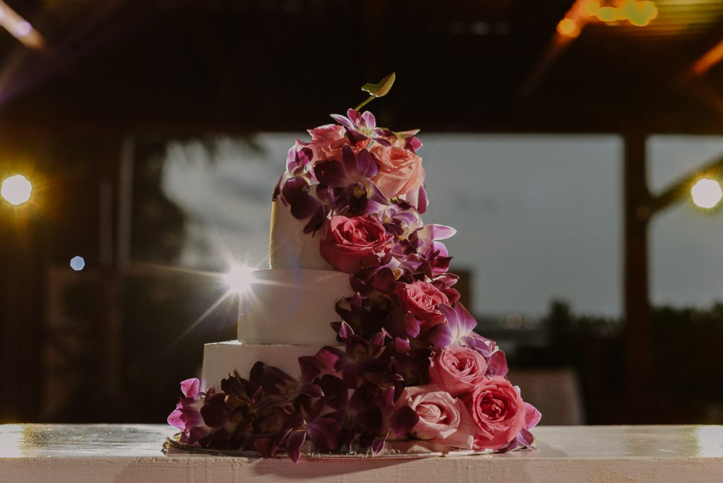 Three tiered wedding cake with fresh flowers at Now Sapphire Wedding. Caro Navarro Photography