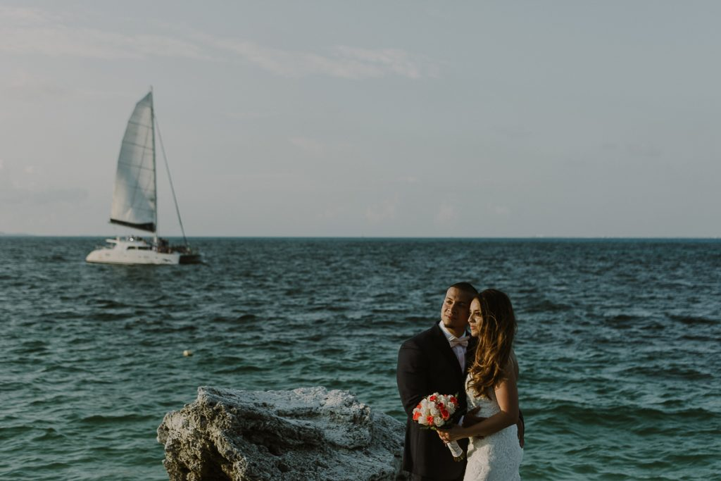 Bride and groom beach portraits with sailboat. Riu Caribe Cancun wedding by Caro Navarro Photography