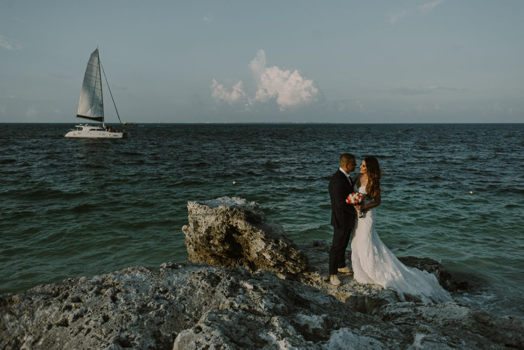 Bride and groom beach portraits with sailboat. Riu Caribe wedding by Caro Navarro Photography