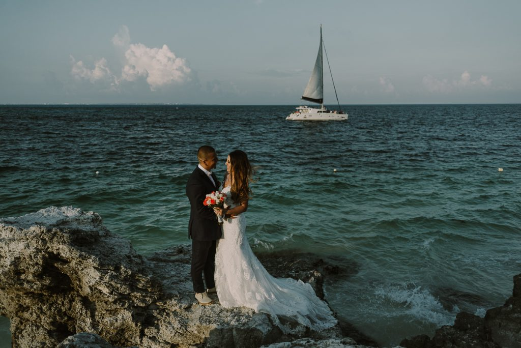 Bride and groom portraits with sailboat. Riu Caribe Cancun wedding by Caro Navarro Photography
