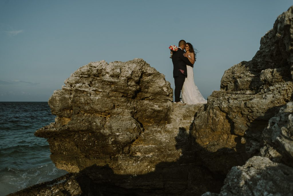 Bride and groom cliff portraits. Cancun destination wedding by Caro Navarro Photography