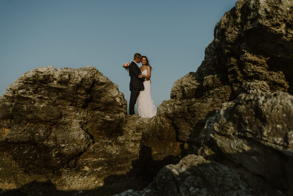 Bride and groom cliff portraits. Riu Caribe Cancun destination wedding by Caro Navarro Photography