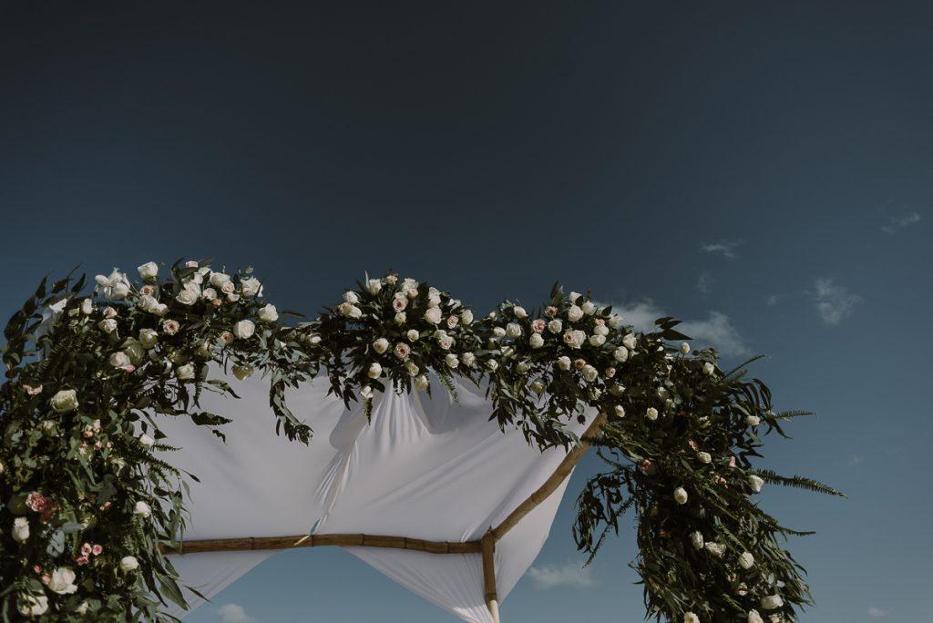 Floral wedding arch at Royalton Riviera Cancun, Mexico. Caro Navarro Photography