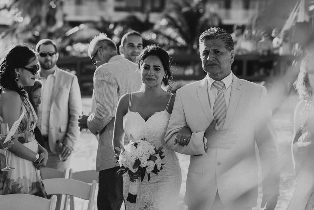 Emotional bride walking down the aisle. Royalton Riviera Cancun wedding by Caro Navarro Photography