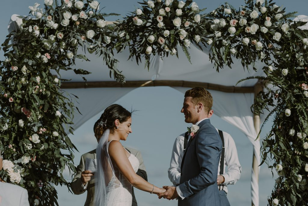 Bride and groom and floral wedding arch at Royalton Riviera Cancun, Mexico. Caro Navarro Photography