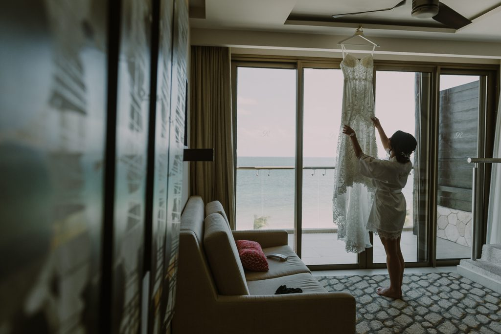 Bride and wedding dress hanging. Royalton Riviera Cancun. Caro Navarro Photography
