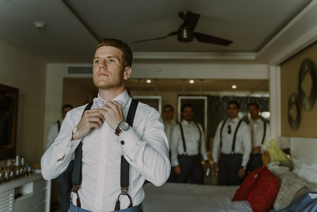 Groom getting ready with groomsmen. Royalton Riviera Cancun Wedding by Caro Navarro Photography