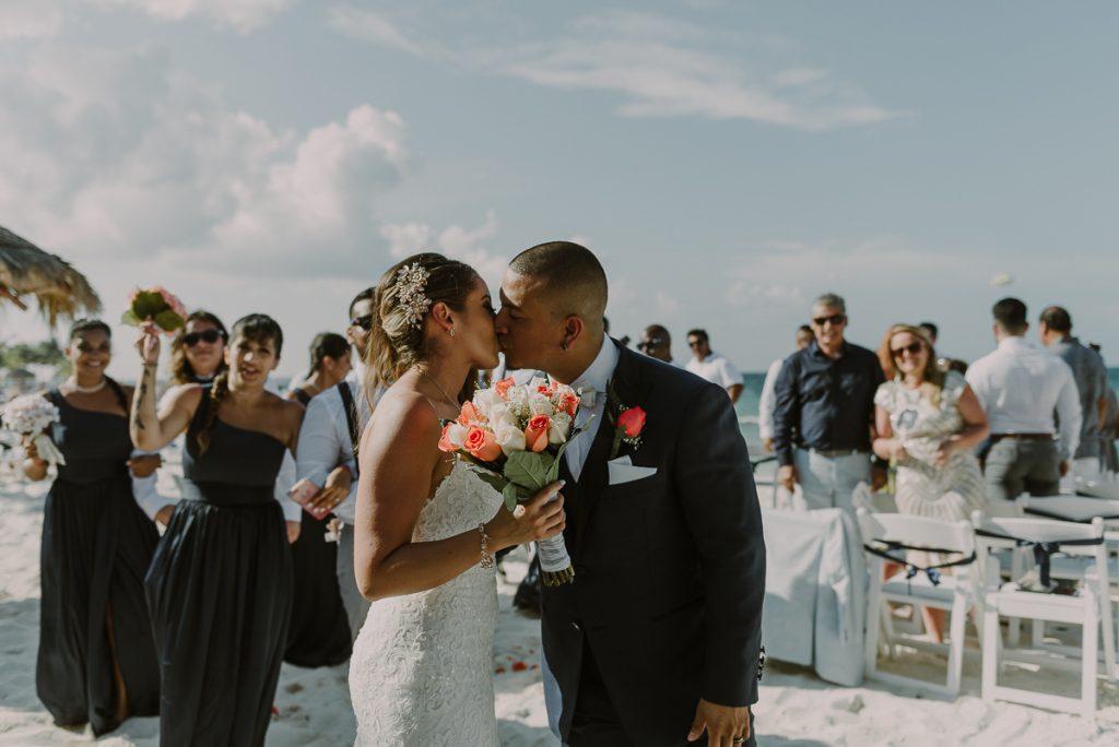 Newlyweds kiss. Riu Caribe Cancun beach destination wedding by Caro Navarro Photography