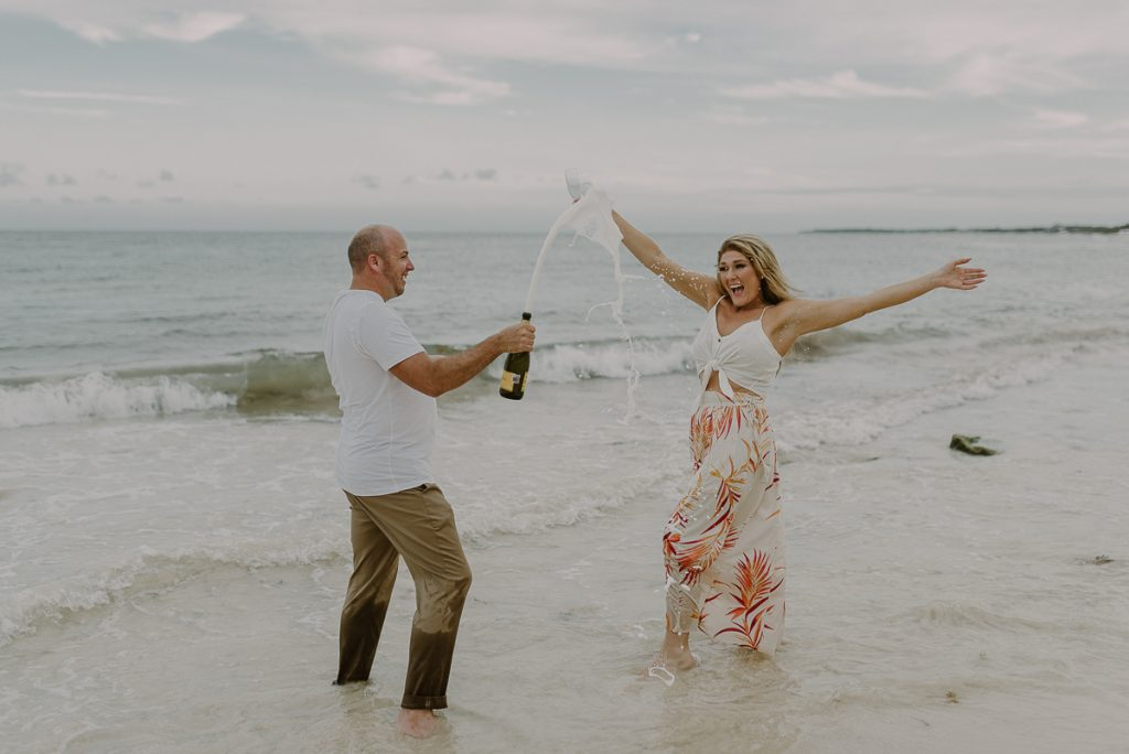 Engaged couple with bottle of champagne in Playa del Carmen, Mexico. Caro Navarro Photography
